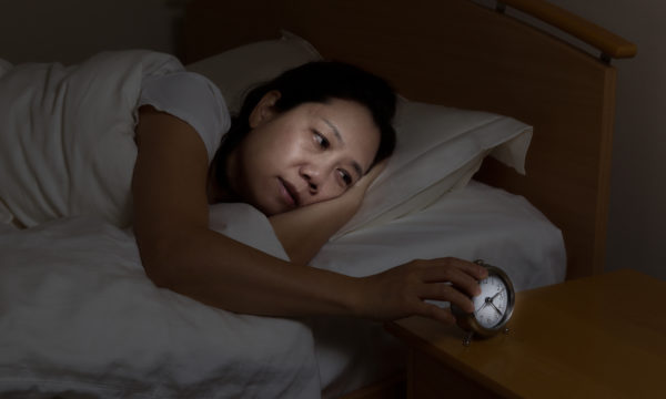 Woman with insomnia touching alarm clock while eyes open.