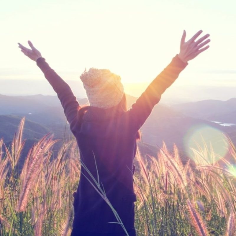 person looking towards mountains with arms raised