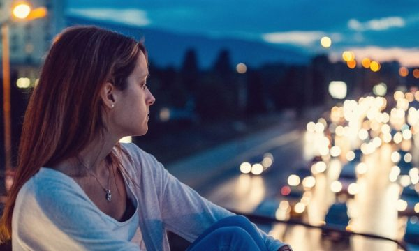 woman looking out window towards traffic at night