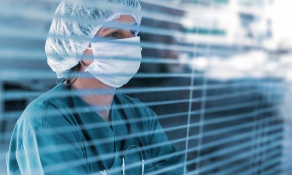 Doctor looking into room through blinds