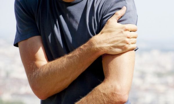 man holding arm in pain