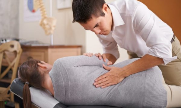 chiropractor adjusting spine of woman
