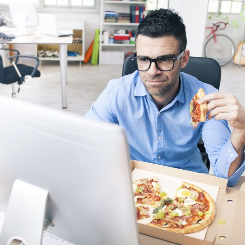 man eating pizza while working at desk