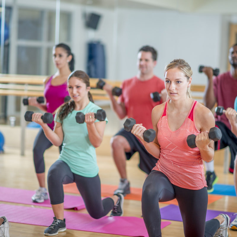 A multi-ethnic group of young adults are working out together in a aerobic fitness class at the gym.