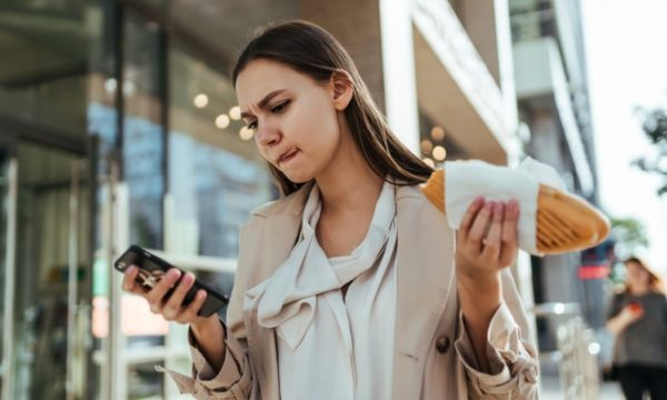 Woman looking at phone, walking, and eating lunch