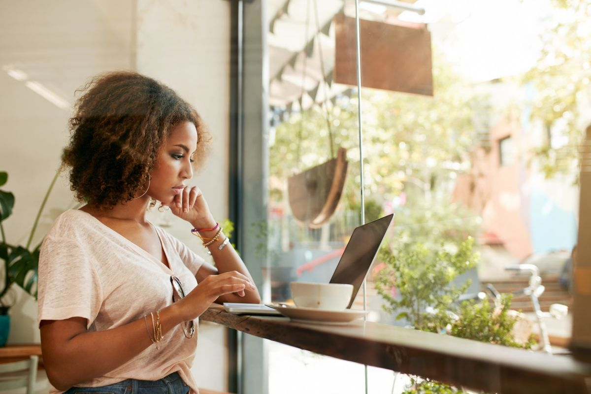 woman on laptop at cafe window