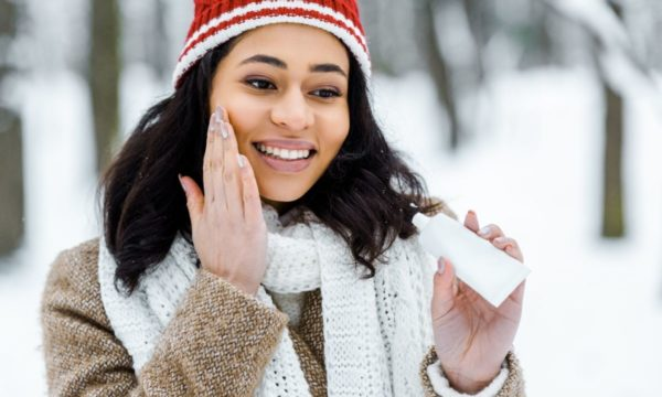 woman putting lotion on face in the winter