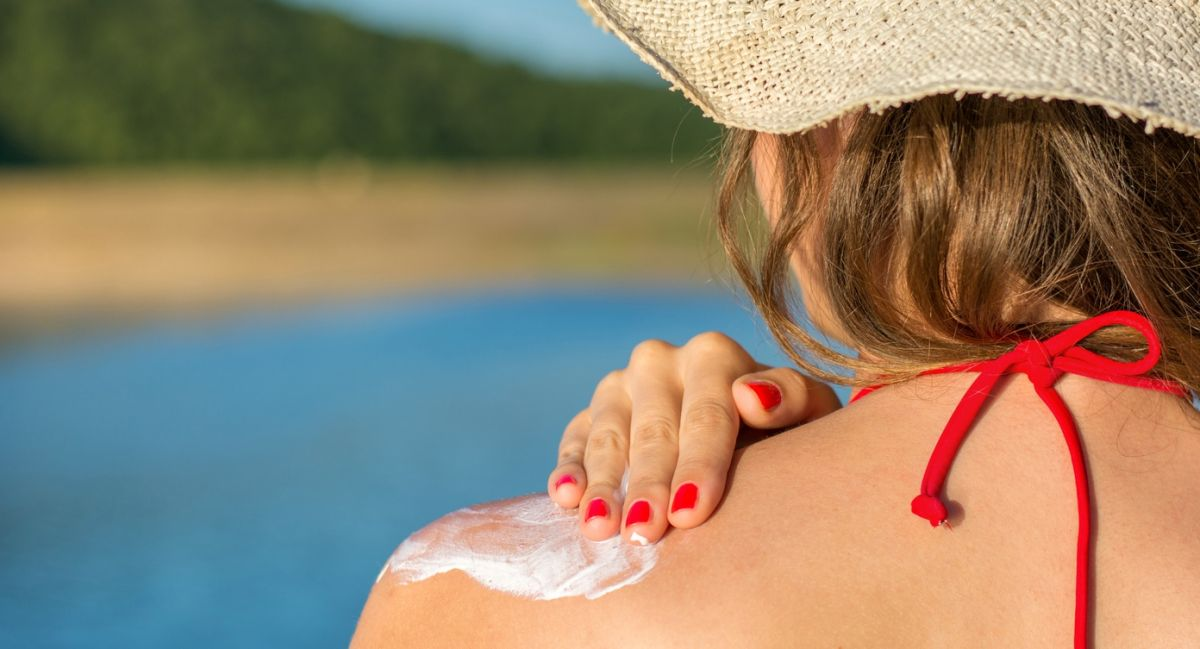 Woman putting sun screen on shoulder
