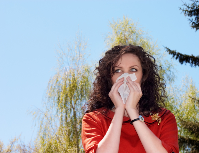 woman with tissue over nose due to sinusitis