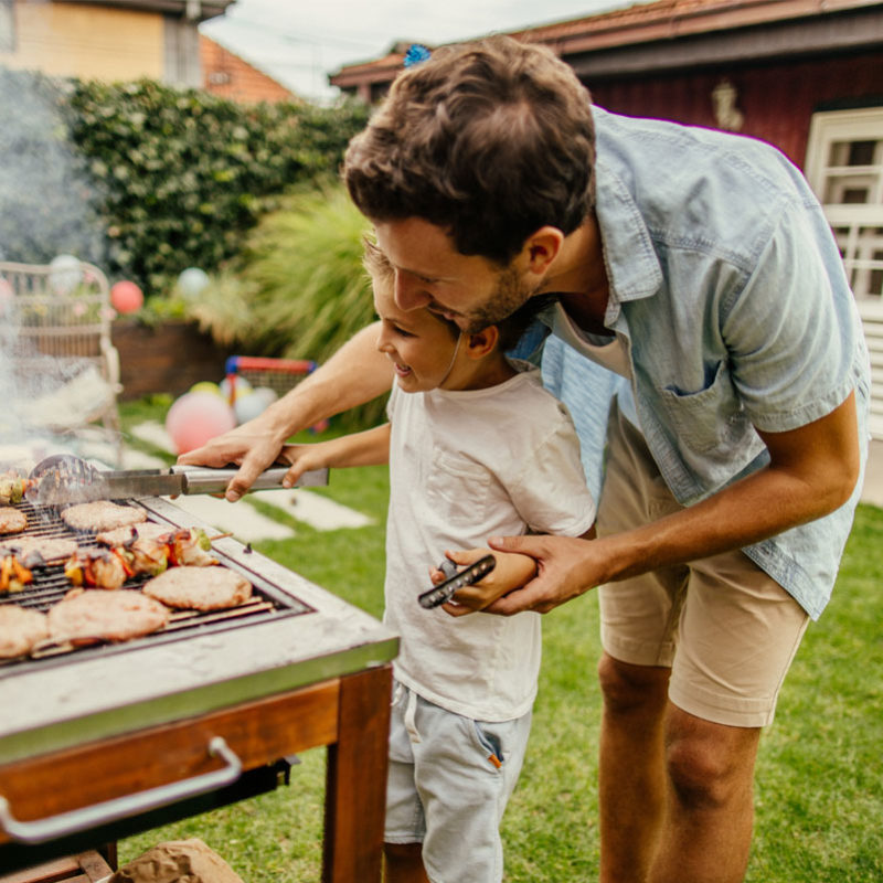 Dad grilling with child