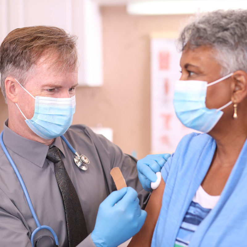 Physician giving older woman a vaccine