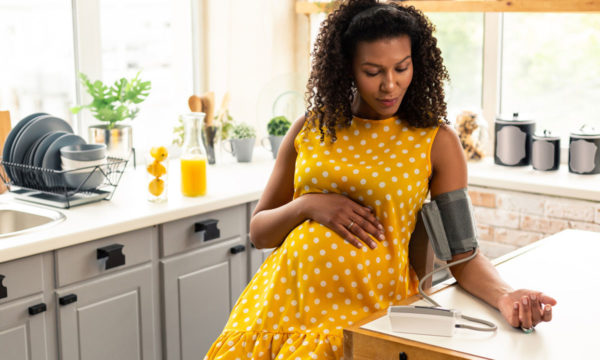 Pregnant woman in kitchen checking blood pressure